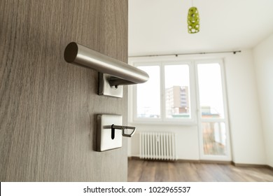 Open wooden oak door leading to empty room with very shallow depth of field