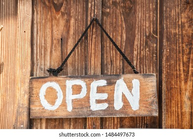 An open wooden sign hanging on a wooden wall.