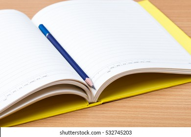 Open yellow diary and blue pencil
