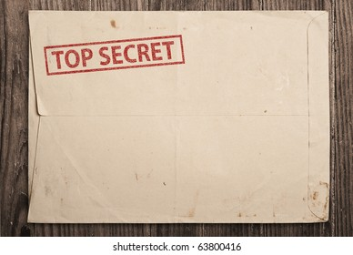 Open yellow envelope with top secret stamp and papers, on wooden table, clipping path.