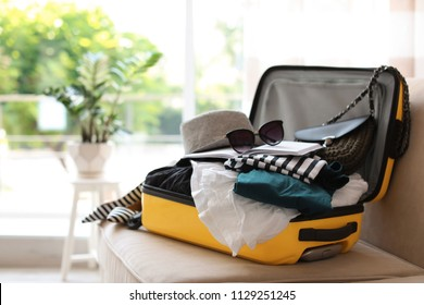 Open yellow suitcase with different clothes packed for journey at home