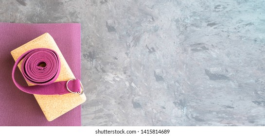 Open yoga mat with cork  block and yoga strap Yoga practice props background. Copy space.