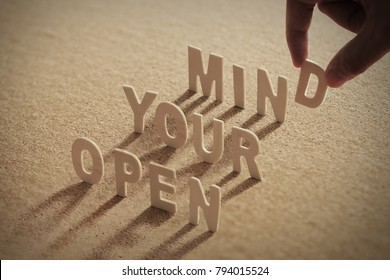 OPEN YOUR MIND wood word on compressed or corkboard with human's finger at D letter.