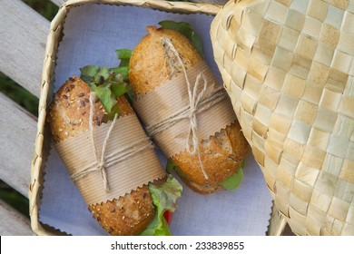 An open-air  express lunch for a vegetarian- whole grain rolls with fresh vegetables and a glass of fresh orange juice. Rolls are hidden in the woven birch basket