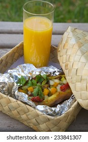 Open-air lunch for a vegetarian- potato baked with vegetables and cheese in an aluminum foil and a glass of fresh orange juice. Dish is hidden in the woven birch basket