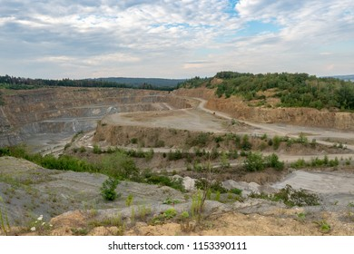 Opencast mining quarry with machinery. Quarrying of stones for construction works. Mining industry in quarry.