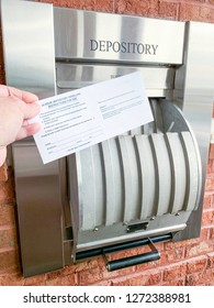 An opened 24-hour drive-thru bank depository with portion of hands and fingers holding a deposit envelope in a horizontal image format.