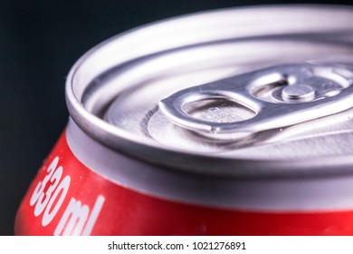 Opened beer, soda or cola red can. Close up, dark and illuminated