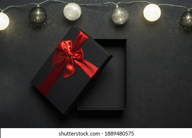 Opened black gift box with red ribbon. Gift on a black granite surface. Christmas lights above the box.