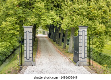 Opened black wrought iron gate between stone pillars. Behind the fence is a driveway covered with light colored gravel leading to an estate in the Netherlands. It is at the end of the summer season.
