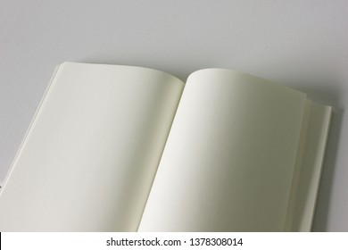 An opened blank eco sketchbook on texture white background, with green-read recycle paper page.