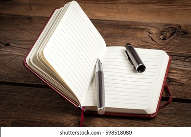 Opened blank notebook with elegant fountain pen on wooden background.