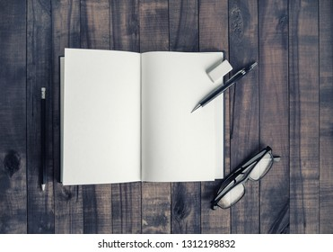 Opened blank notebook, glasses, pencil and eraser. Stationery on vintage wood table background. Flat lay.
