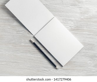 Opened blank notepad and pencil on light wooden background. Flat lay.
