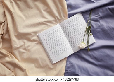 Opened book and beautiful flower on crumpled bed