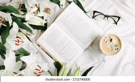 Offenes Buch, Kaffeetasse, Brille und frische Blumen auf dem weißen Bett. Flachlage, Draufsicht