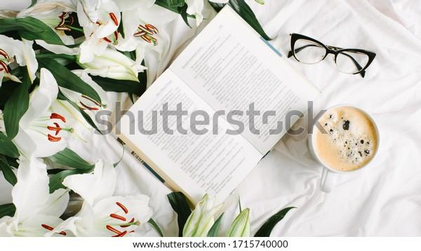 白いベッドに本、コーヒーカップ、眼鏡、新鮮な花を開いた。平面、平面図