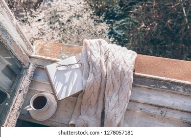 Opened book, cup of tea or coffee, glasses and knitted sweater on window sill over blooming tree view. Cozy spring weekend concept. The text on pages is not recognizable.