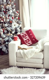 Opened book and a cup of tee on the cozy armchair with warm blanket and cushion on it near Christmas tree