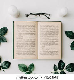 Opened book, glasses, green leaves on white background. Flat Lay