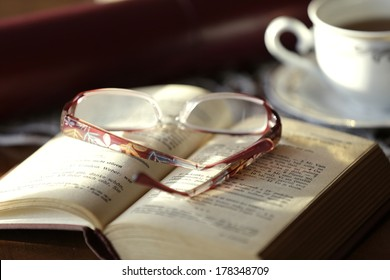 Opened book and glasses, on old wooden table.