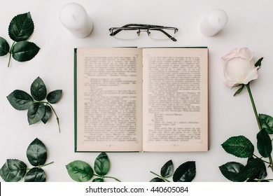Opened book, glasses, pink rose on white background. Flat Lay