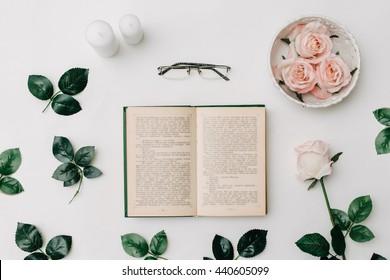 Geöffnetes Buch, Brille, rosafarbene Rosen auf weißem Hintergrund. Flach-Lay