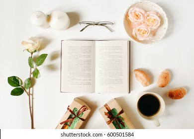 Opened book, glasses, roses, vintage tray, croissants, gifts and coffee cup on white background. Flat Lay, top view, mockup