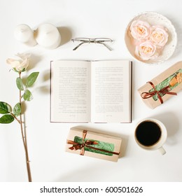 Opened book, glasses, roses, vintage tray, gifts and coffee cup on white background. Flat Lay, top view, mockup