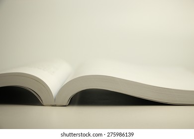 An opened book laying on the blank surface.