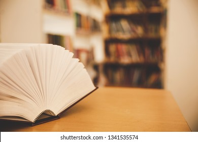 Opened book on the desk and isle of bookshelves in school study class room background for academic education learning concept