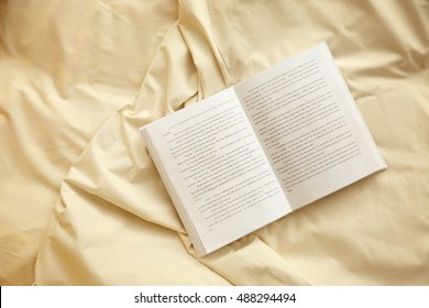 Opened book on light crumpled sheet
