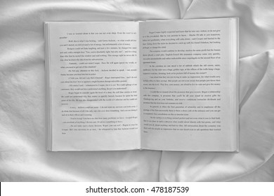 Opened book on white crumpled sheet