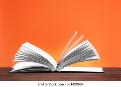 Opened book on wooden table and orange background