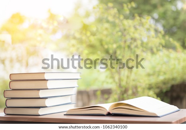 Opened book on wooden table on bright background