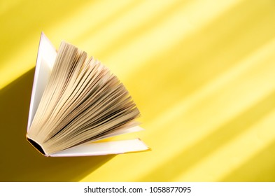 Opened book on a yellow background in the bright sun. The concept of education, reading, buying books.