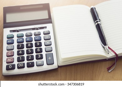 opened book and pen and calculator on wood background