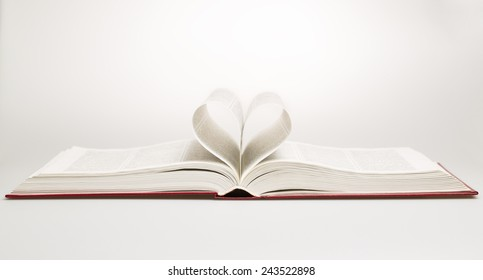 Opened book with sheets in the form of heart, studio shot