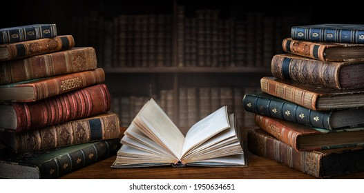 Opened book and stacks of old books on wooden desk in old library. Ancient books historical background. Retro style. Conceptual background on history, education, literature topics.