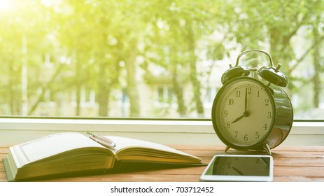 The opened book and standing next to the clock with the phone the concept of study