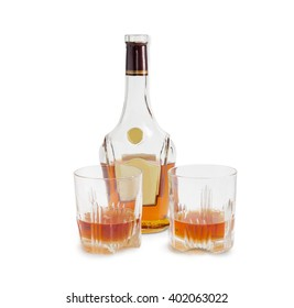Opened bottle of whiskey and two glasses with whiskey on a light background