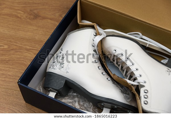 Opened box with new white figure skates for women. The box lies on a light brown wooden background. Selective focus.
