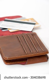 Opened brown leather wallet and credit cards in background.