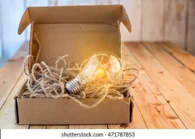 Opened brown paper box with turned on  light bulb inside / New idea concept / Unleashing your idea concept