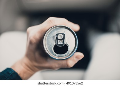 An opened can with some drink with man hand
