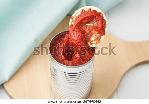 opened can of tomato paste on wooden round cutting board
