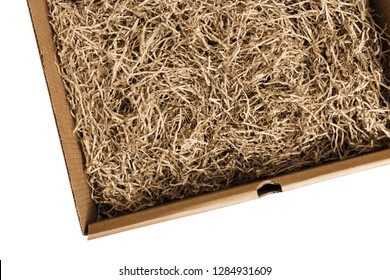 Opened cardboard box with decorative shredded paper for gifting and stuffing. Top view.
