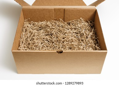 Opened cardboard box with decorative shredded paper for gifting and stuffing.