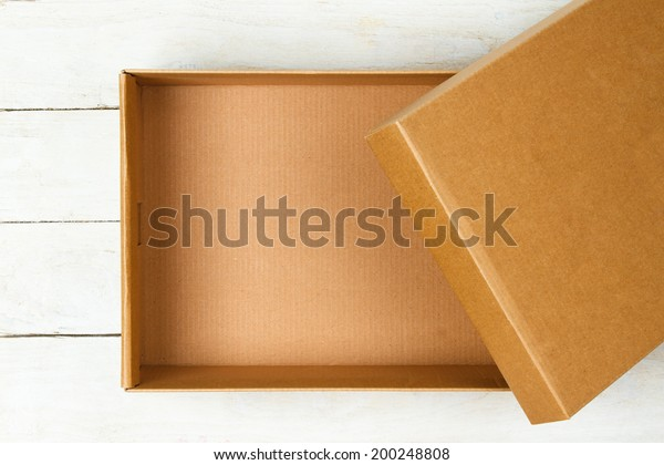 Opened cardboard box on a wooden table