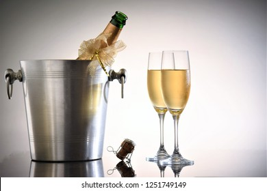 opened champagne bottle in cooler tank with glasses on gray background
